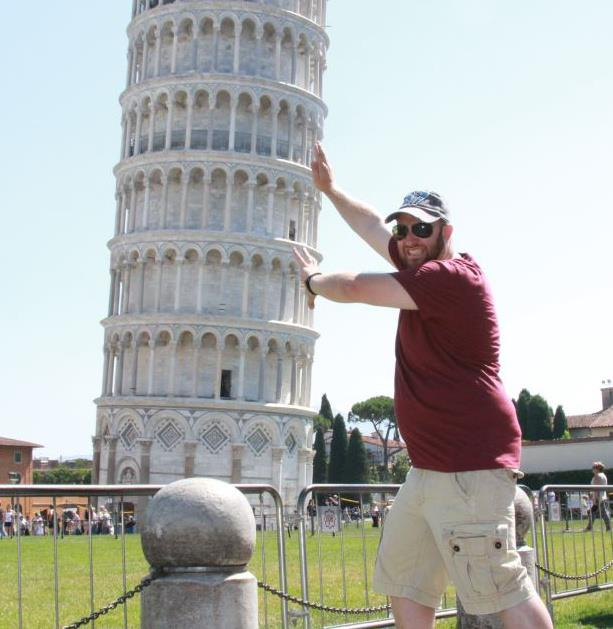 Man posing in front of leaning Tower of Pisa with hands held up diagonally as if he is holding up the building.